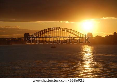 Sydney Harbor ( Harbour ) Bridge with spectacular golden brown sunset - stock photo