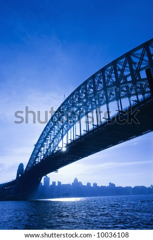 Sydney Harbour Bridge at dusk with view of distant skyline and harbour in Sydney, Australia. - stock photo