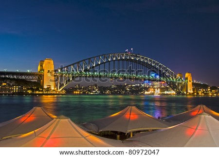 Sydney Harbour Bridge viewed from Circular Quay from behind lighted umbrellas - stock photo
