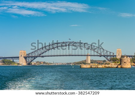 Sydney Harbour Bridge with beautiful sunny blue sky. Fort Denison in the foreground on the right. Fort Denison is a former penal site and defensive facility occupying a small island. - stock photo