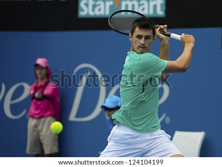 SYDNEY - JAN 9: Bernard Tomic from Australia hits a backhand in his second round match in the APIA Sydney Tennis International. Sydney January 9, 2013. - stock photo