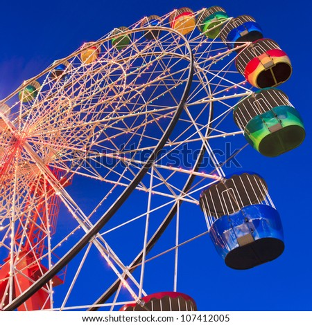 sydney luna park attraction wheel at sunset illuminated with lights in motion segment of circle - stock photo