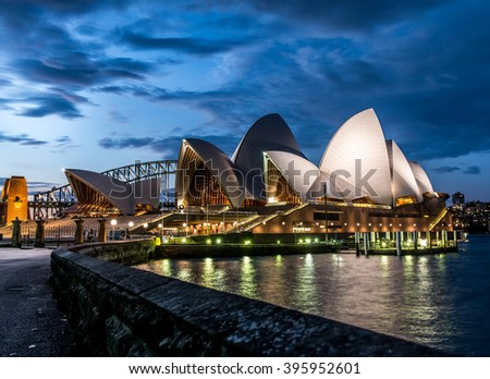 SYDNEY - MARCH 24: View of the iconic Sydney Opera House after sunset from the Royal Botanical Garden, with the Sydney Harbour Bridge in the background, on March 24, 2016 in Sydney, Australia. - stock photo