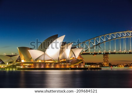SYDNEY - MAY 16: Opera House and Harbor Bridge at twilight on May 16, 14 in Sydney. The two man made structures are considered as the major landmark of Sydney and tourists attraction. - stock photo