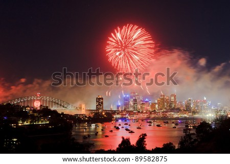 Sydney new year fireworks big red ball of pyrotechnics fire flashes above city, harbour and bridge - stock photo