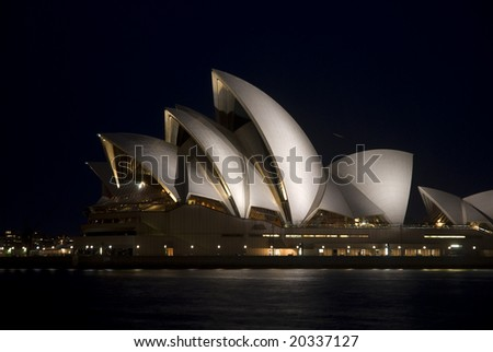 SYDNEY, November 11, 2008 - Night horizontal side view of floodlit Sydney Opera House with harbour in foreground. Photographed in Sydney, Australia on 11 November, 2008. - stock photo