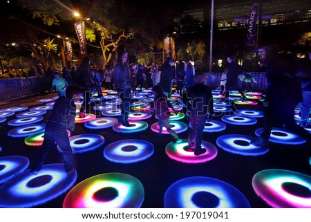 SYDNEY, NSW, AUSTRALIA - JUNE 2, 2014;  Pool at Vivid Sydney. Each circle is independent and  interacts with participants movements. It senses how heavily you land,  quickly you leap and bound.   - stock photo
