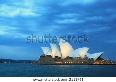 Sydney Opera House at dusk with cloudy skies overhead - stock photo