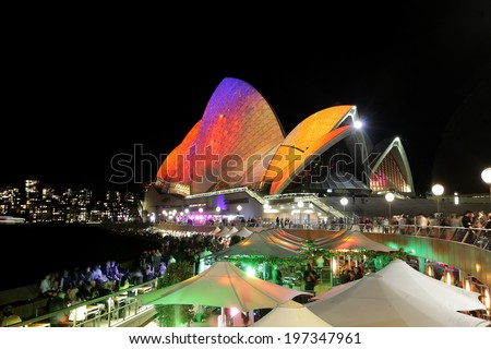 SYDNEY OPERA HOUSE, AUSTRALIA - MAY 28, 2014 -  Vibrant visual imagery and colours light up the Sydney Opera House sails during Sydney Vivid Festival.  Crowds of locals and tourists on  foreshore.   - stock photo
