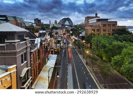 Sydney's The Rocks historic residential district and suburb at sunset from above position with lights on and Harbour bridge in a distance - stock photo