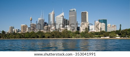 Sydney skyline, blue sky and Sydney Harbor water reflections. New South Wales, Australia.