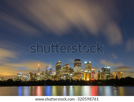 Sydney Skyline, Sydney Landmark, Sydney Tower and Sydney City CBD at night with blue sky blur cloud long exposure and Reflection From circular quay from Mrs Macquarie's Chair in Summer, Australia  - stock photo