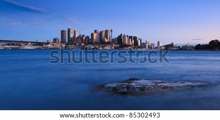 Sydney twilight view over harbor with stone at high tide blurred waves sea water and illuminated skyscrapers - stock photo