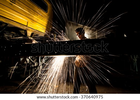 SYLHET, BANGLADESH- APRIL 10, 2014: A young boy was welding to fix a truck at the late night inside a roadside truck garage. - stock photo