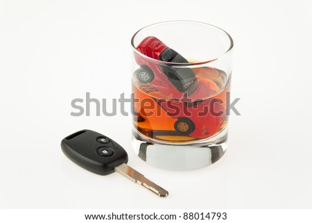 symbol for drunken driving. a car and a carkey in a glass - stock photo