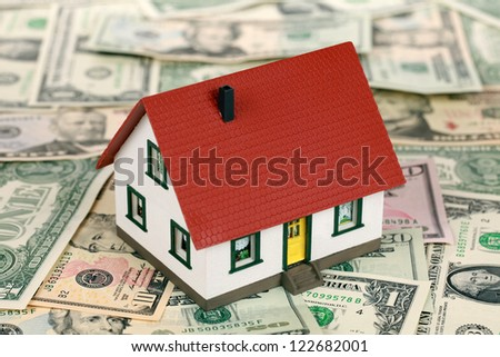 Symbol for home financing with a house on Dollar notes - stock photo