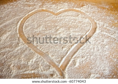 Symbol heart painted in flour on baking - stock photo