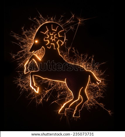 Symbol of a ram created with sparks and fire set on black background. - stock photo