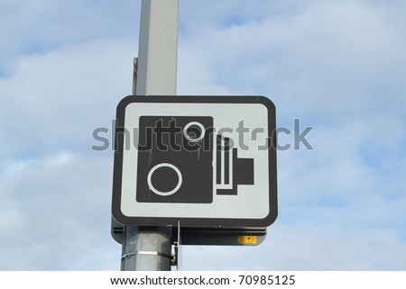 Symbol of a speed camera in black, on white, on a square sign attached to a post against a cloudy sky. - stock photo