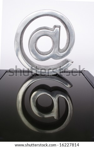 Symbol of arroba reflected over black crystal - stock photo