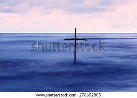 symbol of Baptism, a wooden cross in the Jordan River - stock photo