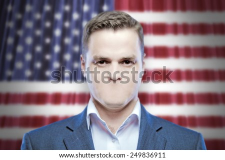 Symbol of censorship and freedom of speech: a young man without a mouth on a background of the national flag of USA (America) - stock photo