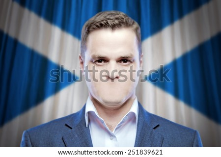 Symbol of censorship and freedom of speech: a young man without a mouth on a background of the national flag of Scotland - stock photo