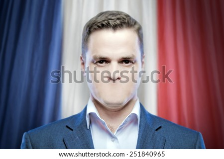 Symbol of censorship and freedom of speech: a young man without a mouth on a background of the national flag of France - stock photo