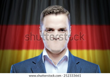 Symbol of censorship and freedom of speech: a young man without a mouth on a background of the national flag of Germany - stock photo