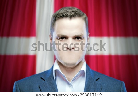 Symbol of censorship and freedom of speech: a young man without a mouth on a background of the national flag of Denmark - stock photo
