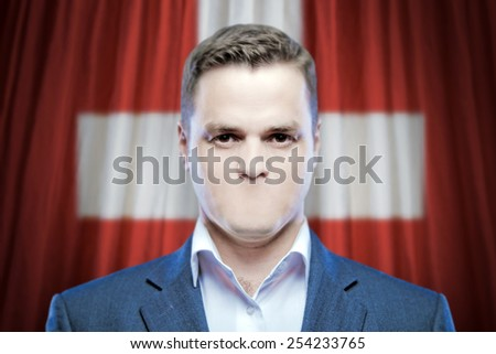 Symbol of censorship and freedom of speech: a young man without a mouth on a background of the national flag of Swiss - stock photo