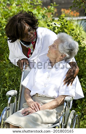 Symbol of comfort and support from care giver talking to elderly woman outdoor - stock photo