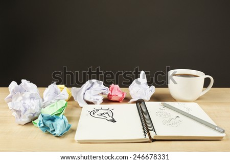 Symbol of idea as light bulb in notebook with crumpled paper on wooden desk and dark background - stock photo