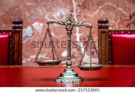 Symbol of law and justice on the red table, law and justice concept, focus on the scales - stock photo