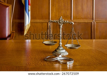 Symbol of law and justice with handcuffs on the table - stock photo