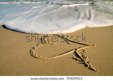 Symbol of love on sand. - stock photo