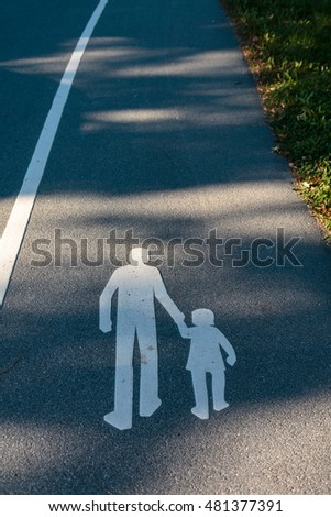 Symbol of parent walking with child on street