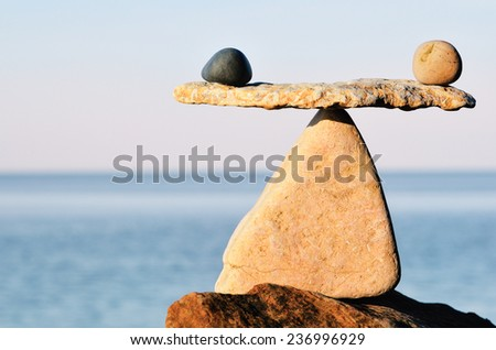 Symbol of scales is made of pebbles on the sea boulder  - stock photo