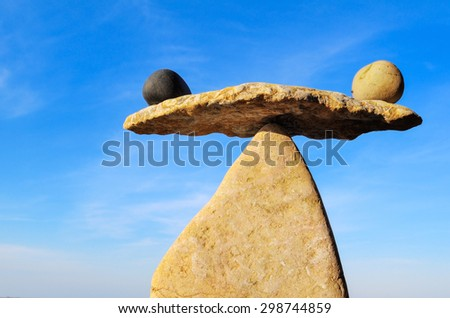 Symbol of scales is made of pebbles on the seacoast  - stock photo