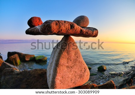Symbol of scales is made of pebbles on the seashore - stock photo