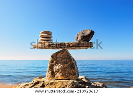 Symbol of scales is made of stones on the boulder  - stock photo