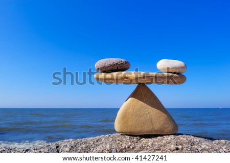 Symbol of scales is made of stones on the cliff - stock photo