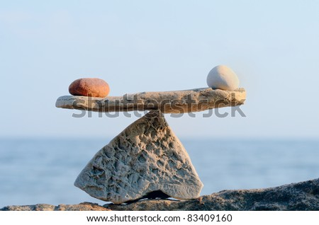 Symbol of Scales is made of stones on the top of boulder - stock photo