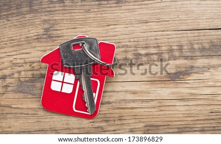 Symbol of the house with silver key on wooden background  - stock photo