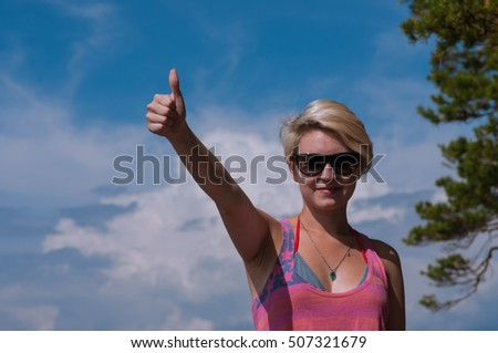 symbol ok hand girl on a background of blue sky