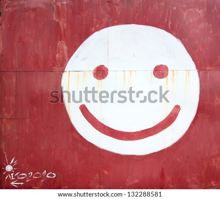 Symbol smiley face painted on a fence - stock photo