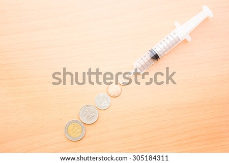 symbolic financial crisis theme with a big syringe filled with money - stock photo