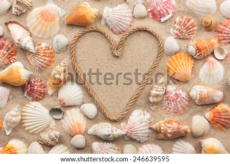 Symbolic heart made from rope and seashells lying on the sand, as background - stock photo
