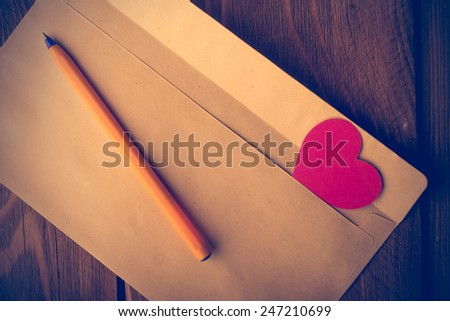 Symbolic heart of cardboard inserted into the envelope. Valentine's Day.  Retouching in retro style - stock photo