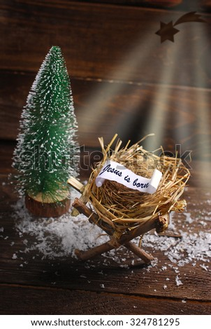 """symbolic nativity scene with inscription"""" Jesus is born"""" on  rolled paper lying on a hay in the manger instead of baby Jesus and  light rays of Bethlehem star on wooden background - stock photo"""